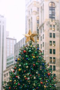 decorated christmas tree against urban multistage building facades